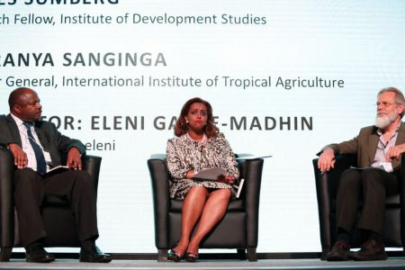 Picture of DG Nteranya Sanginga (left) on the debate floor with Eleni Gabre-Madhin (moderator) and Jim Sumberg (right)