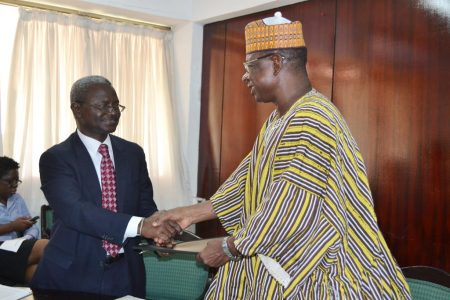 Photo of IITA's Asamoah Larbi and the Deputy Minister of Environment, Science and Technology Information, Dr Alfred Tia Sugri, shake hands after the signing.