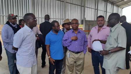 Picture of Chiji Ojukwu of AfDB (center) and H.E. Matata Ponyo (left) listen to IITA's Nzola Mahungu (right), IITA Representative in DR Congo, talking about the cassava processing equipment introduced through the SARD-SC project funded by AfDB.