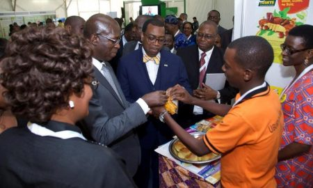 Picture of Akinwumi Adesina (center) samples SARD-SC cassava products.