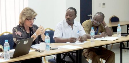 Picture of World Bank's Sara Simons giving an overview of funding opportunities in Tanzania as IITA's Freddy Baijukya and Victor Manyong listen intently