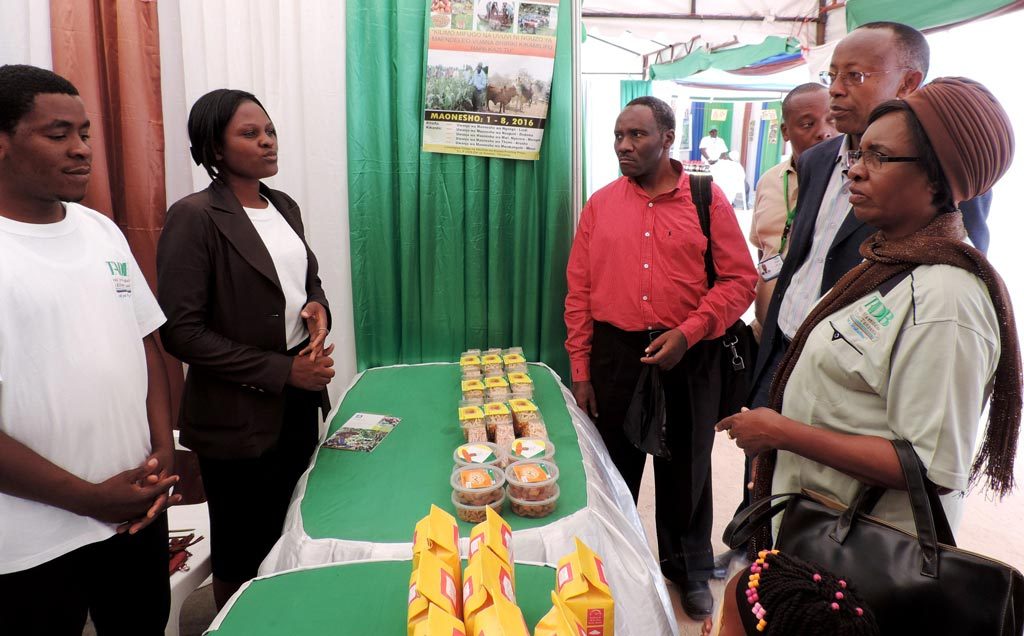 Picture of Board chair and the MD of the Tanzania Agricultural Development Bank (TADB) listening to TYA youth on their activities and products.