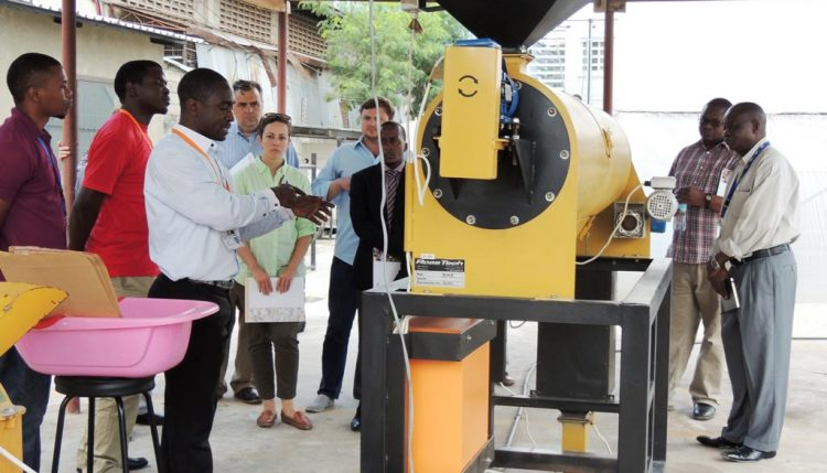 Picture of IITA staff demonstrate to the visiting team the production of AflasafeTZ at IITA-EA hub in Tanzania.
