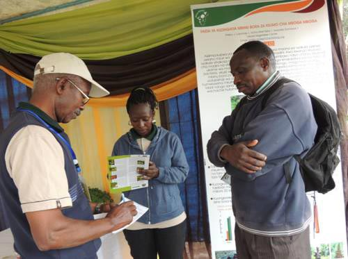 Picture of Festo Ngulu, Africa RISING Babati coordinator noting down information given by Paskali, a farmer from Mananga village-Babati