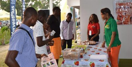 Picture of Agripreneurs Sandrine (in green) and Lisette (in red) briefing the visitors to the IYAKIN exhibition stand.