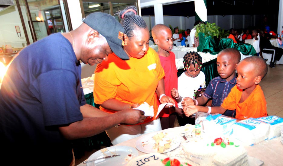 Picture of Manyong giving children of staff pieces of the 50th Anniversary cake.