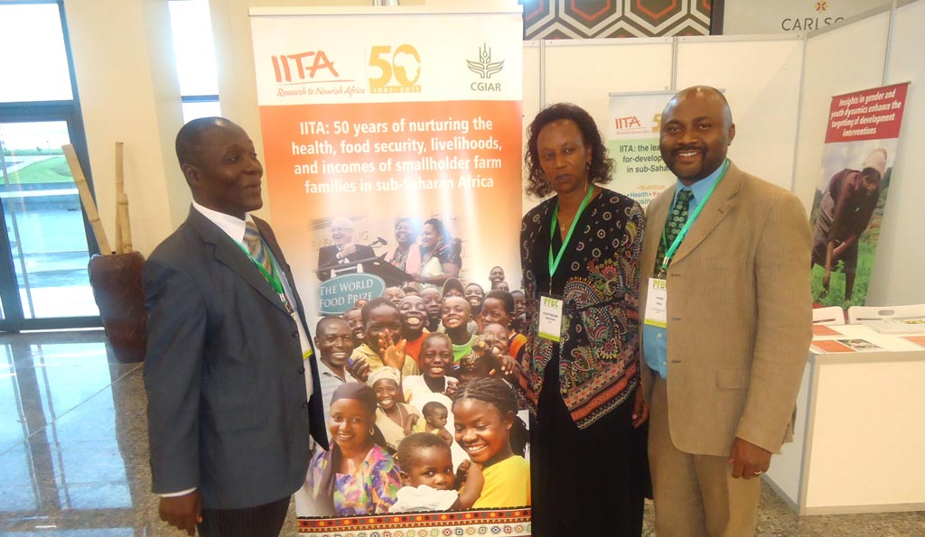 Picture of Denis Sonwa of CIFOR (Left), and Kantengwa Speciose IITA Rwanda (center), with a visitor at the IITA exhibition booth during the event at Kigali.