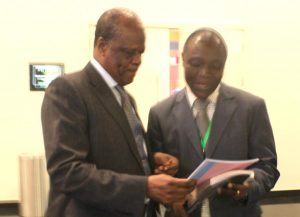 Picture of Denis handing IITA annual report to the Minister.