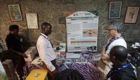 Picture of Kayode Are explaining the information products produced by IAR&T at the display of materials produced by the various partners during the project.