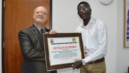 Picture of Afolabi presenting a certificate of credence to IITA on behalf of all Nigerian undergraduates.