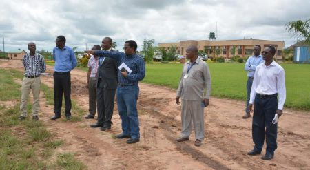 Picture of Chikoye explaining to Chief Kaputa (in a suit) about the different cassava varieties being tested at the IITA-SARAH campus.