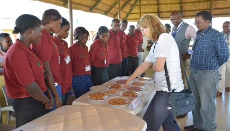 "Picture of The Zambia IITA Youth Agripreneurs (ZIYA) Program successfully conducted a training course on cassava value addition for 11 ZIYA members―all female―on 6–16 March at the IITA Southern Africa Research and Administration Hub (SARAH) campus in Kabangwe, Lusaka Province. The 11 women came from different youth groups from Kaoma District in Western Province, Monze District in Southern Province, and Serenje and Mkushi districts in Central Province partnering under the ZIYA umbrella. T he training course was conducted with support from the Support to Agricultural Research for Development of Strategic Crops in Africa (SARD-SC) project. Facilitators included Emmanuel Alamu, Food Scientist; Prisca Chileshe, Postharvest Utilization Research Assistant; Nhamo Nhamo, ZIYA Youth Coordinator; and Jeremiah Hantolo, Zambia SARD-SC Maize Coordinator, all based at IITA-SARAH. The 10-day, hands-on course covered the various steps in preparing cassava-based food products―from root preparation (cleaning, peeling, chipping, and drying) to processing and cooking/ baking. Specifically, the youth were taught how to make confectionary products such as biscuits, chin-chin, fritters, titbits, and cupcakes. At the end of the training, the trainees presented the different food products that they had produced to IITA-Zambia staff as well as to Hilde Koper-Limbourg, Deputy Director General for Corporate Services, who coincidentally was also in Zambia on a familiarization and monitoring trip to the southern Africa Hub. ""These are very impressive products that you have prepared,"" David Chikoye, IITA Southern Africa Regional Director, said during the presentation by the trainees. ""I sincerely hope that you will apply what you've learned here―and what you will still learn in the future from ZIYA―in your respective groups when you go back,"" he added. ""These are really delicious,"" added Koper-Limbourg. ""I see a really good business opportunity for these products, and a great business venture for the ZIYA youth. You should be proud of yourselves and what you have accomplished here."" Asked what they will do with the knowledge that they gained from this training, Caroline Liwena, ZIYA Youth Chair, who also participated in the course, related that they would also train other members of their respective youth groups. ""Apart from echo training, we will also start some small businesses producing and selling these food products. And, of course, start making money,"" she proudly added."