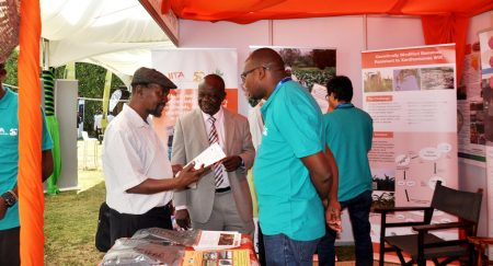 Picture of IITA's Manyong (middle) hosts guests at the exhibition booth.