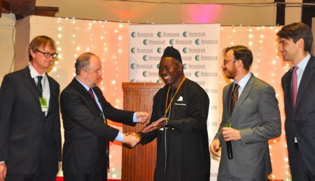 Picture of Okechukwu and Dalberg and Ford Foundation representatives giving award plaque to winner of the challenge from NRI