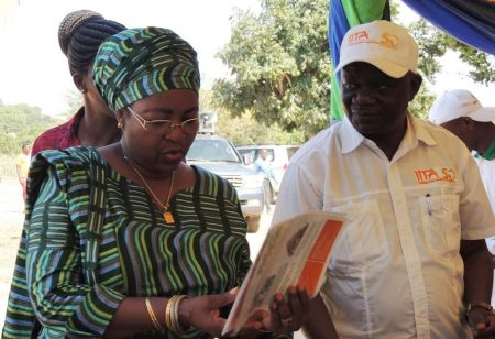 Picture of Victor Manyong explaining to the former first lady, Salma Kikwete, IITA's research on aflasafe, an effective biocontrol agent for reducing aflatoxin contamination.
