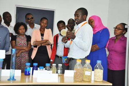 Picture of Jacob Njegela, Research Associate at IITA, explains how aflasafe was developed and manufactured in the lab at IITA East Africa hub.