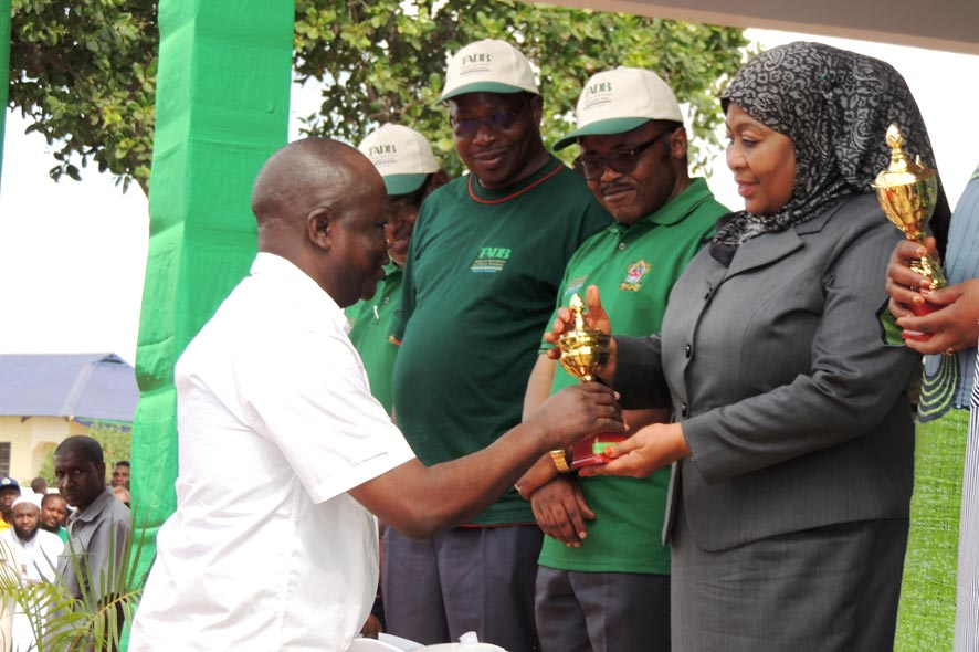 Picture of Manyong receiving IITA's trophy from the Tanzanian Vice president, Hon. Samia Suluhu Hassan. Looking on are the Hon. Ministers of Agriculture and Finance.