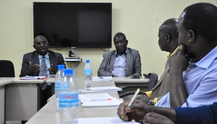 Picture of the Permanent Secretary (left) and his team members briefing the IITA delegation.