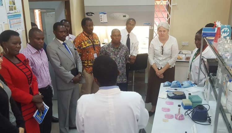 Picture of Jocelyn Brown (second from right) listens to a technician's briefing during the lab visit.