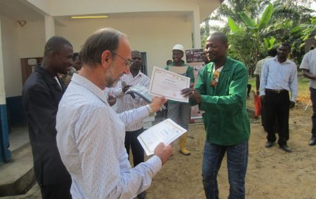 Picture of A farmer receiving a certificate during the graduation after a series of farmers field school training by PROSICA in Cameroon.