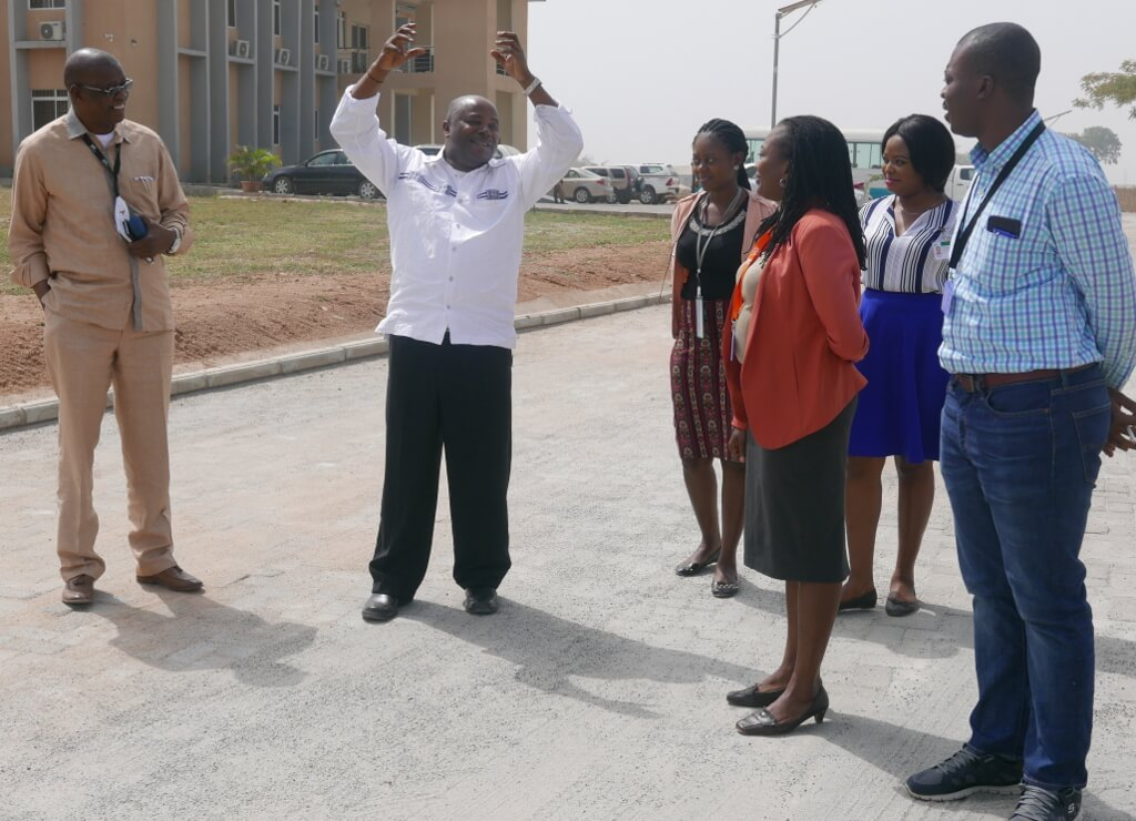 Picture of DG Sanginga (with raised arms) and staff at the Abuja Station on one of the newly constructed roads.