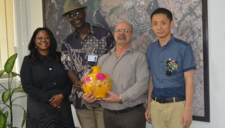 Picture of Special adviser to Oyo State Governor on project and bureau of investment promotions Tolu Sadipe (left), and one of the Chinese investors (right) presenting a souvenir to IITA management.