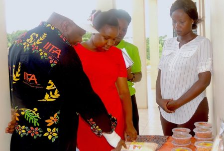 Picture of Youth Agripreneurs showcase some of their products to the DG (left)