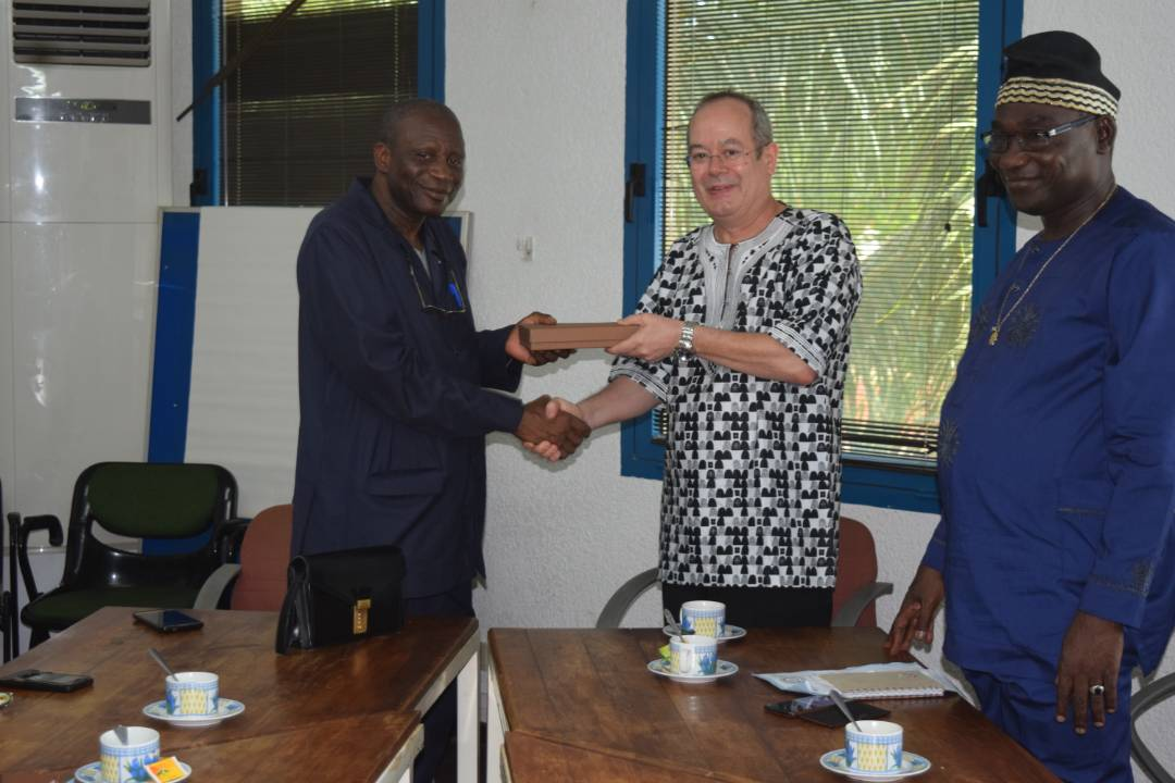 Picture of IITA-Benin Country Representative Manuele Tamo presents a token to UNA Vice-Chancellor, Professor Gauthier Biaou