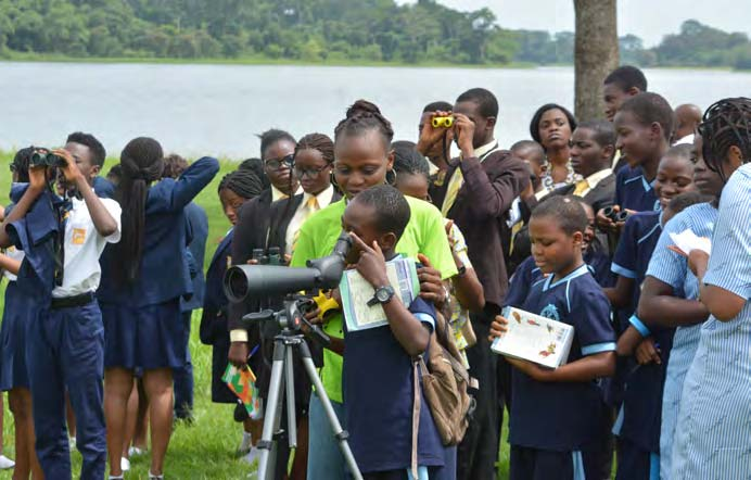 Picture of Students using binoculars to watch migratory birds during the bird watching session at IITA lake side
