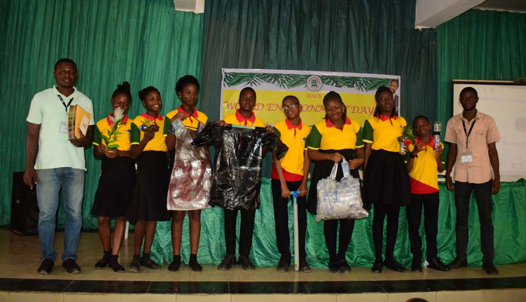 Picture of students, with Forest Center team members, displaying items made from plastic waste. Photo O.Olubodun