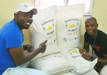 Picture of Two COPAKIN agripreneurs showcasing 25-kg bags of high quality semolina.
