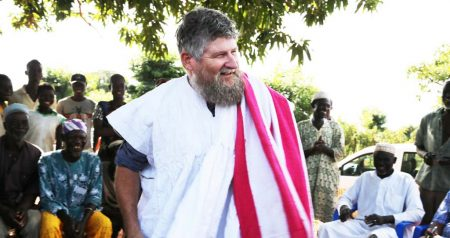Picture of Farmers in Cheyohi Community in the Northern Region of Ghana ceremonially dressed Jerry Glover in the traditional Ghanaian smock