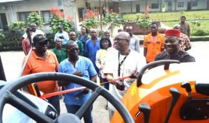 Picture of Gbassey Tarawali cutting the ribbon as staff members look on
