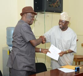 Picture of Alfred Dixon, Director, P4D Office (left), and Owolabi Oladejo, the President and Founder of MBS (right), shaking hands after the MoU signing