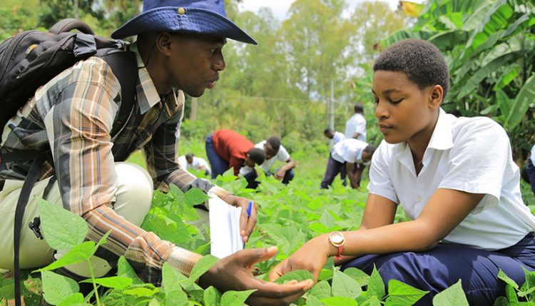 The founder of NEWDAY Afrika, Prince Bobo Tangabanga, talking to a secondary school student on the school farm.