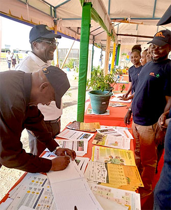 TARI Director General, Dr Geoffrey Mkamilo standing and TARI Board Chairman, Dr Yohane Bulena signing the visitors' book at the IITA exhibition booth.