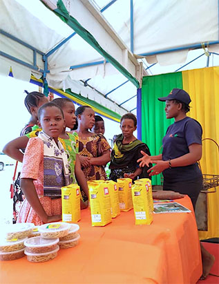 Veronica Kebwe, Chair of the Tanzania Youth Agripreneurs explaining the group's activities and products to visitors.